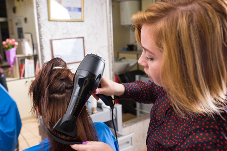 blow dryer: Close Up of Blond Stylist Drying Hair of Young Female Brunette Client Using Brush and Hand Held Blow Dryer in Salon