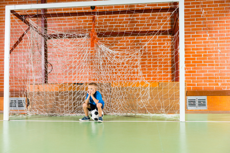 indoor soccer: Bored young boy waiting on an indoor soccer court sitting glumly on the ball in the goal as he waits to start practicing