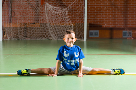 supple: Proud little boy doing the splits on an indoor sports court smiling as he demonstrates how supple he is