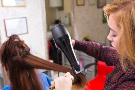 hair stylist: Close Up of Young Blond Stylist Drying Long Hair of Brunette Client Using Handheld Blow Dryer in Salon