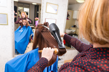 full length mirror: Rear View of Young Blond Stylist Drying Hair of Brunette Client Using Handheld Blow Dryer and Round Brush in Salon with Out of Focus Reflection in Large Full Length Mirror in Background