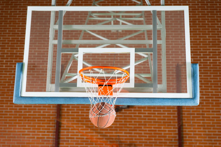 backboard: Basketball passing through the net on the goal post in front of a transparent backboard on an indoor court Stock Photo