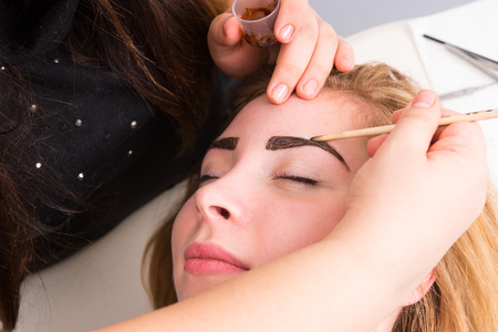 esthetician: Close Up of Esthetician Filling in Eyebrows of Female Client with Dark Brown Make Up During Eyebrow Spa Treatment - Blond Client Looks Contented and Relaxed Stock Photo