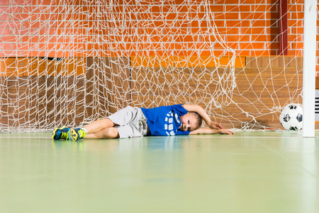 allowing: Young goalkeeper lying on his side on the floor in the goalposts missed the ball allowing through a goal, with copy space Stock Photo
