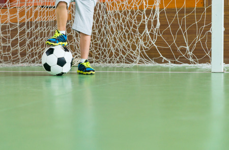 child feet: Young goalkeeper on an indoor court standing with one foot resting on the soccer ball, low angle view of his legs with copy space