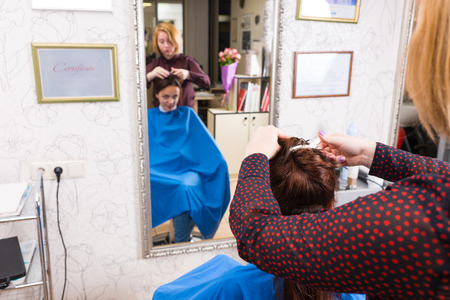 full length mirror: Rear Close Up View of Stylist Styling Hair of Young Brunette Client in Salon with Out of Focus Reflection in Large Full Length Mirror