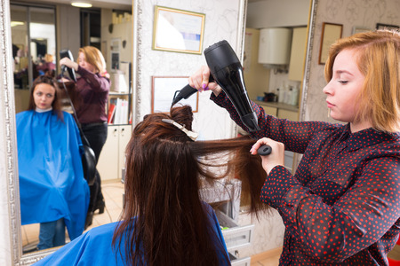 full length mirror: Young Blond Stylist Drying Hair of Brunette Client Using Handheld Blow Dryer in Salon with Out of Focus Reflection in Large Full Length Mirror in Background