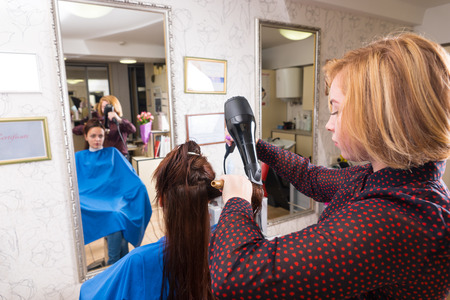 blow dryer: Rear View of Blond Stylist Drying Hair of Young Female Brunette Client Using Brush and Hand Held Blow Dryer in Salon