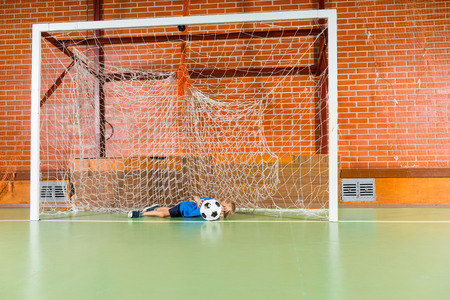 diving save: Young soccer goalkeeper practicing his skills on an indoor court diving to save the ball in the goalposts