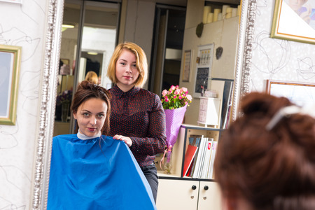 smock: Portrait of Young Blond Stylist Standing Behind Young Brunette Female Client Wearing Blue Smock and Sitting in Chair in Salon - Reflection in Large Mirror