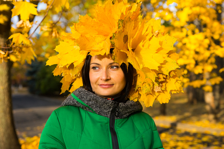 anorak: Smiling pretty young woman with a hat of colorful bright yellow fall leaves posing outdoors in an autumn park, head and shoulders portrait