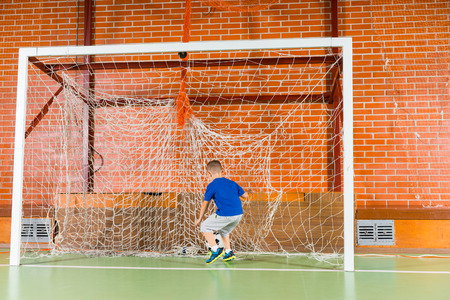 all weather: Little boy practicing his soccer skills dribbling and kicking the ball in the goalposts on an indoor all weather court, back to the camera