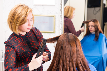 hair stylist: Serious Blond Stylist Using Flat Iron on Hair of Brunette Woman in Salon with Reflection of Client in Background Mirror