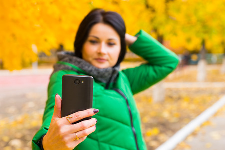 anorak: Attractive woman taking an autumn selfie on her mobile phone as she poses in front of colorful yellow trees, focus to her hand and the phone