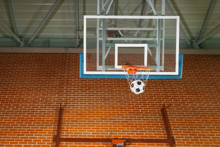 scored: Shooting a basketball goal with a soccer ball passing through the net on an indoor court in a conceptual image
