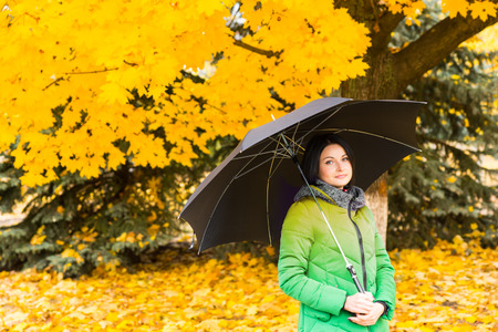 sheltering: Young woman standing in a colorful fall park in front of bright yellow fall foliage sheltering under her umbrella Stock Photo
