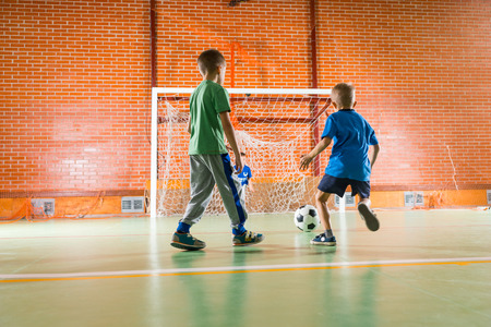 all weather: Two young boys playing soccer together on an all weather indoor court making a run for the goalposts Stock Photo