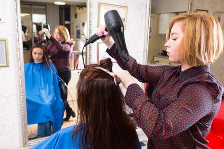 blow dryer: Young Blond Stylist Drying Hair of Brunette Client Using Handheld Blow Dryer in Salon with Out of Focus Reflection in Large Full Length Mirror in Background