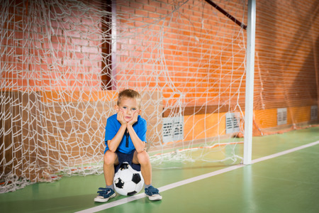 indoor soccer: Glum bored young boy sitting waiting in the goalposts on an indoor soccer court waiting for his team or friends to arrive