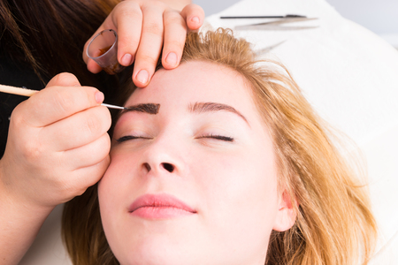dyeing: Close Up of Esthetician Filling in Eyebrows of Female Client with Dark Brown Make Up During Eyebrow Spa Treatment - Blond Client Looks Contented and Relaxed Stock Photo
