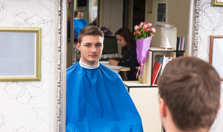smock: Portrait of Confident Looking Young Man Wearing Blue Protective Smock in Hair Salon in Reflection of Mirror