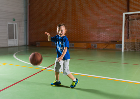 Laughing young boy playing basketball on an indoor court as he runs along bouncing the ball and grinning at the camera 스톡 콘텐츠