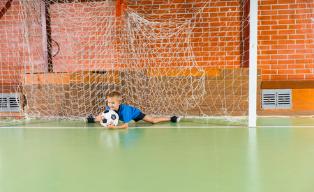 splayed: Young boy saving a goal in a soccer game lying on the floor of the indoor court clasping the ball with his legs splayed in the splits