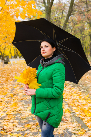 anorak: Attractive woman posing in an autumn park with her umbrella and a handful of colorful bright yellow leaves Stock Photo