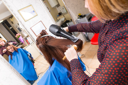 blow dryer: Rear View of Young Blond Stylist Drying Hair of Brunette Client Using Handheld Blow Dryer and Round Brush in Salon with Out of Focus Reflection in Large Full Length Mirror in Background