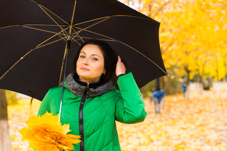 anorak: Attractive young woman enjoying the autumn weather taking a stroll through a park with colorful yellow foliage carrying an umbrella