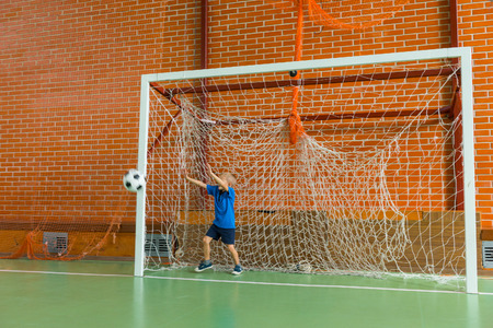 all weather: Young soccer goalkeeper practicing indoors on an all weather court as he leaps to save the ball , with copy space