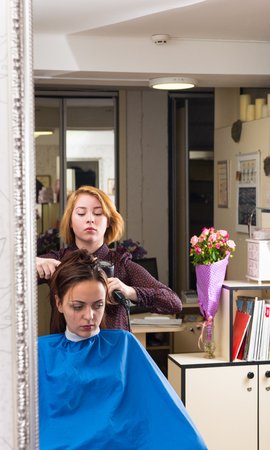 hair stylist: Reflection of Young Blond Stylist Drying Hair of Brunette Client Seated in front of Large Mirror in Salon