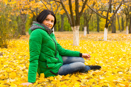 sitting on the ground: Pretty young woman relaxing in an autumn park sitting on the ground amongst bright yellow leaves smiling at the camera