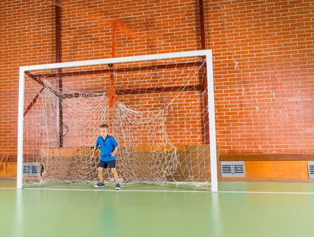 indoor soccer: Young boy standing at the ready in the goalposts of an indoor soccer court as he anticipates a player taking shot at goal