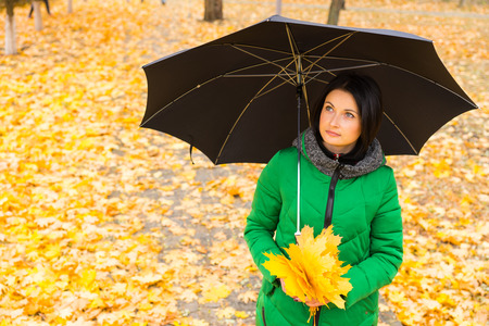 anorak: Pretty serene young woman standing looking up under a black umbrella as she strolls through an autumn park collecting yellow leaves