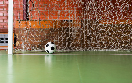 indoor soccer: Soccer ball inside the goalposts against the back net on an indoor soccer court in a red brick building