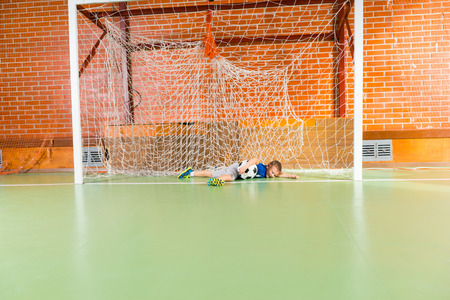 all weather: Young goalkeeping practicing indoors on an all weather court diving to save the ball, with copy space
