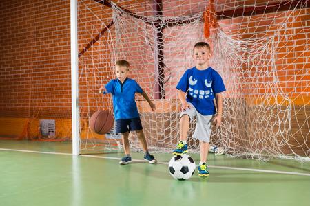 ゴールポスト、サッカー ボール、バスケット ボール、他の常任をバウンス 1 つで遊んで屋内裁判所の二つのスポーティな若い男の子