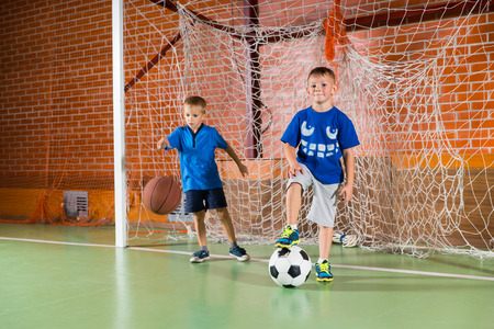 Two sporty young boys on an indoor court playing in the goalposts, one bouncing a basketball and the other standing on a soccer ball Stock Photo