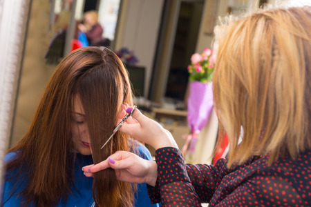 hair dresser: Close Up of Blond Stylist Cutting Hair of Young Brunette Client - Hair Dresser Cutting Angled Bangs into Hair of Young Female Client in Salon Stock Photo