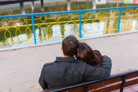 courting: Romantic young couple enjoying a date sitting in a close embrace on a park bench overlooking a lake, view from behind