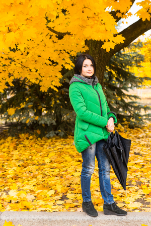 anorak: Trendy young woman walking through an autumn park with her umbrella on a footpath running past trees covered in vivid yellow foliage Stock Photo