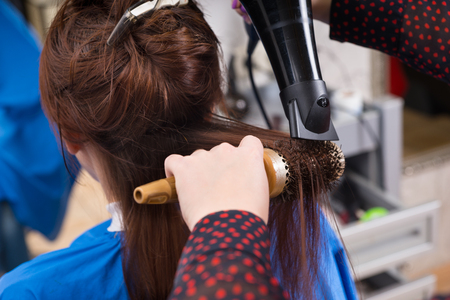 Close Up Rear View of Brunette Woman Having Wet Hair Brushed and Dried by Stylist Using Round Brush and Hand Held Blow Dryer in Salon