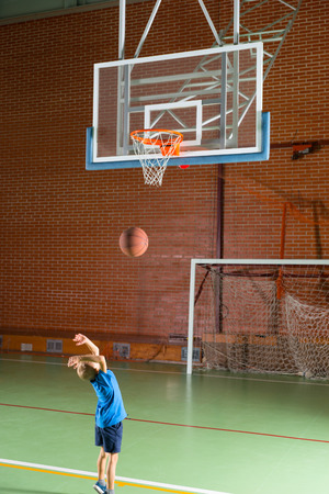all weather: Young boy playing basketball indoors on an all weather court shooting for the net as he practices for school