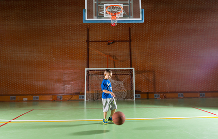 goalpost: Small boy playing basketball walking along bouncing the ball below the goalpost on an indoor court in a red brick building Stock Photo