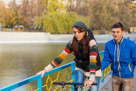 alongside: Young Man Helping Young Woman to Ride Bicycle with Aid of Colorful Railing on Bridge Over Pond in Urban Park on Chilly Autumn Day