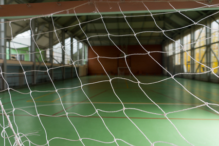 all weather: View of an empty indoor sporting facility with an all weather green court viewed through the net in the goal Stock Photo