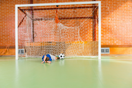 indoor soccer: Young goalkeeper missed the soccer ball allowing through a goal on an indoor soccer court as he lies on the ground between the posts Stock Photo