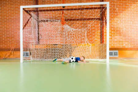 indoor soccer: Young goalkeeper playing indoor soccer diving between the goalposts to save the ball, with copy space Stock Photo