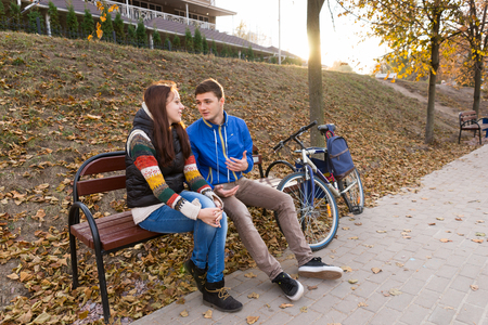 tryst: Young Couple in Conversation Sitting Together on Bench Next to Bicycle in Urban Park with Bright Setting Sun in Background on Chilly Autumn Day